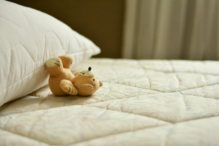 ベッドとクマのぬいぐるみ